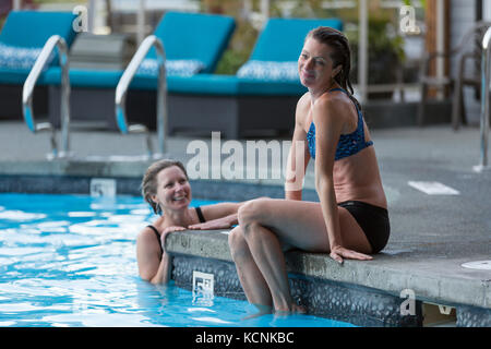 Two girlfriends relax at the outdoor pool while visiting the Kingfisher Resort and spa.  The Comox Valley, Vancouver - Stock Photo