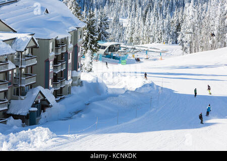 Skiers and snowboarders scoot past slopeside accommodations on Mt. Washington's Linton's Loop, The Comox Valley, - Stock Photo