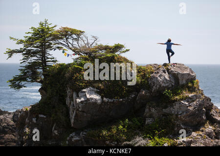 A visitor to the Amphrite Lighthouse and Pacific Wild Trail in Ucluelet practices her yoga and takes in the ocean - Stock Photo