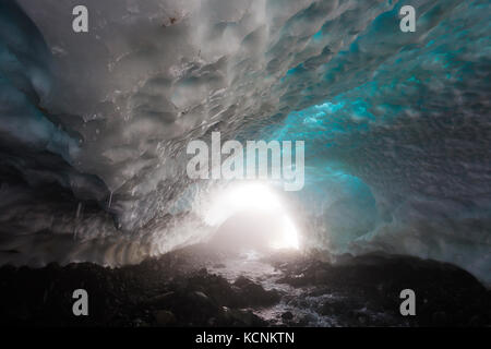 Ice water drips from the roof of a snow cave at the base of Century Sam lake, Strathcona Park, Vancouver Island, - Stock Photo