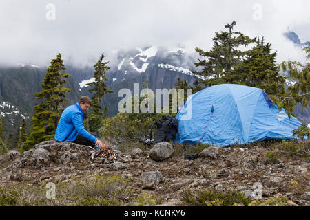 A young hikers tend to a fire while camping on Lee Plateau, Vancouver Island, British Columbia, Canada. - Stock Photo