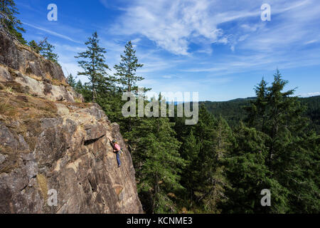 A female rock climber ascends a route on one of the climbing areas near Chinese Mountain.  Quadra Island. - Stock Photo