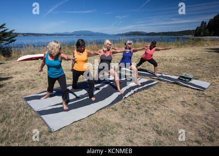 Five female friends practice Yoga while camping on Quadra Island, Canada - Stock Photo