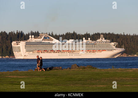 A couple strolls along a walkway on Tyee Spit while a princess cruiseline ship passes through Discovery Passage, - Stock Photo