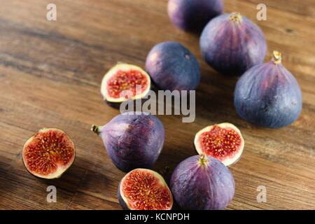 Ripe blue and purple figs, both whole and cut in half, randomly spilled on dark wood table - Stock Photo