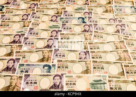 Japanese banknotes of various amounts laid out forming background. - Stock Photo