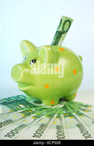 Green piggy bank with banknotes - Stock Photo