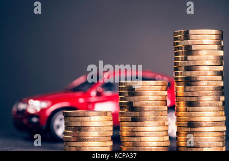 Rising piles of coins and a red car in the background - Stock Photo