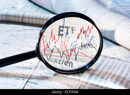 Magnifying glass shows the courses of ETF, funds and shares - Stock Photo