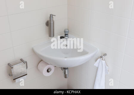 Hydrant and sink in a small toilet, used and slightly dirty - Stock Photo