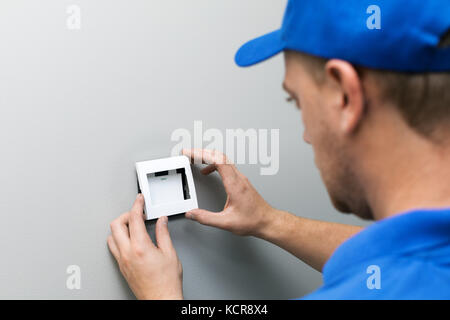 electrician in blue uniform installing light switch on the wall - Stock Photo