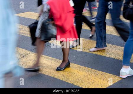 Blurry legs of  people walking on zebra crossing on city street - Stock Photo