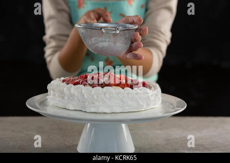 Mid-section of woman icing sugar on tart - Stock Photo