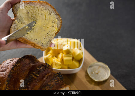Close-up of woman applying butter over multigrain bread slice - Stock Photo
