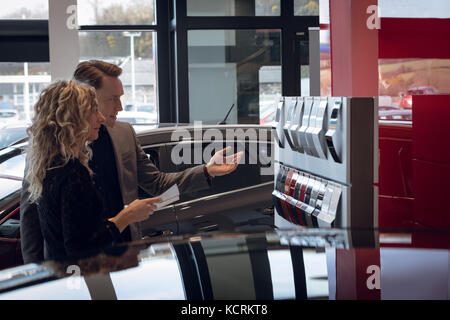 Female customer looking at color swatch while standing by salesman in car showroom - Stock Photo