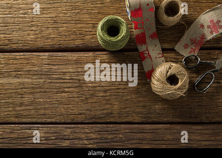 Thread and jute spools with scissor on wooden table - Stock Photo
