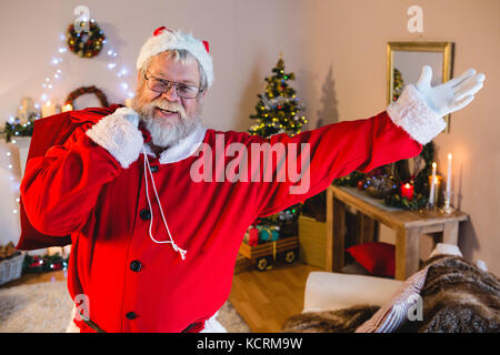 Portrait of santa claus doing welcoming gesture while carrying his gift sack - Stock Photo