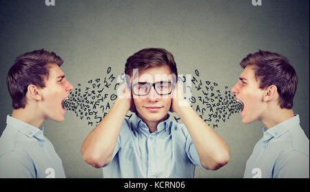 Two angry men screaming at peaceful guy covering his ears with hands ignoring them, alphabet letters coming out - Stock Photo