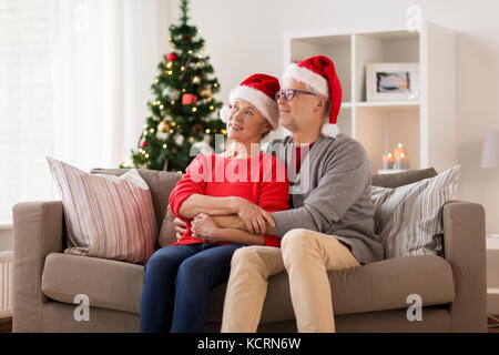 happy senior couple in santa hats at christmas - Stock Photo
