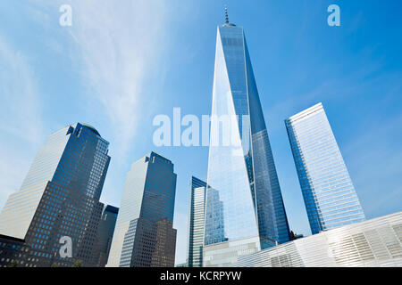 One World Trade Center skyscraper surrounded by glass buildings, blue sky in a sunny day in New York - Stock Photo