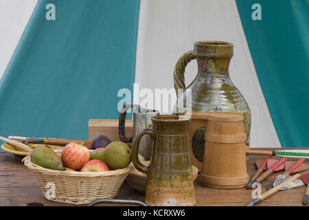 Apples and pears in a wicker basket on a table with pottery tankards - Stock Photo