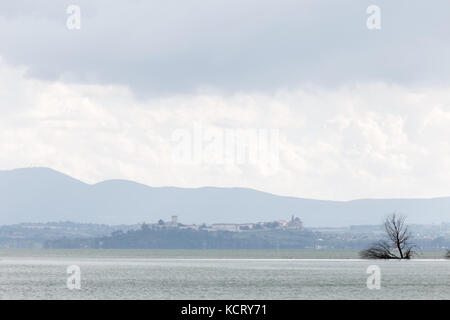 View of Castiglione del Lago town (Umbria, Italy), with Trasimeno lake and trees in the foreground - Stock Photo