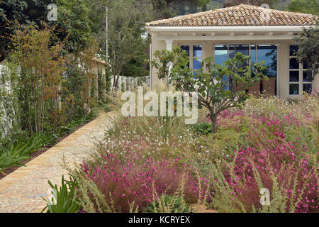a beautiful holiday bungalow or home on the beach in Kassiopi on the greek island of Corfu. Rambling gardens and - Stock Photo