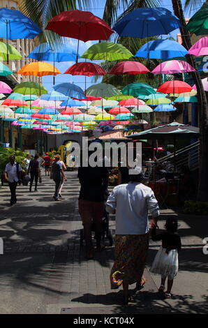 Port Louis, Mauritius - tourists and shoppers walk in an umbrella covered lane in the Le Caudan Waterfront in the - Stock Photo