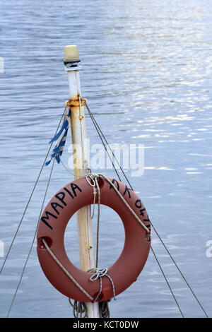 an orange perry buoy or life ring belt on the mast of a small pleasure or fishing boat in the greek harbour at sidari - Stock Photo