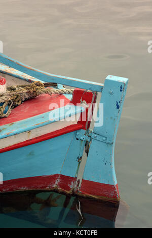 a Greek fishing boat in a harbour on the island of Corfu painted in a blue and red colour and in a traditional style. - Stock Photo