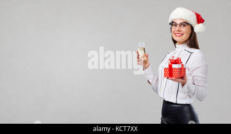 A girl in a santa hat with a glass of champagne and a gift in he - Stock Photo