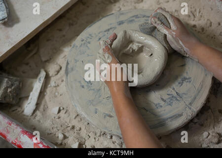 Hands of girl using sponge while molding a clay - Stock Photo