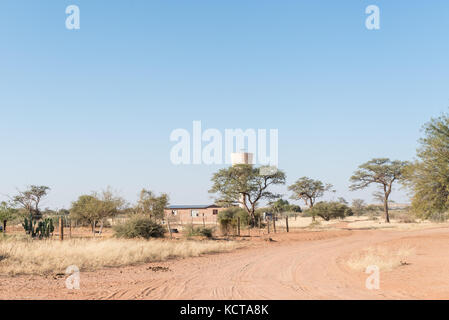 A street scene with a house and water reservoir in Koes, a small town in the Karas Region in Namibia - Stock Photo
