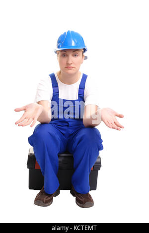 Female builder wearing blue helmet and jumpsuit sitting on toolbox spreading hands hopelessly over white - Stock Photo