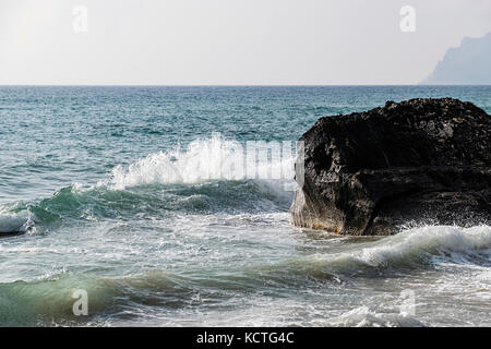 Scenic View Of Ionian Sea With Waves Splashing On Cliff Against Moody Sky - Stock Photo