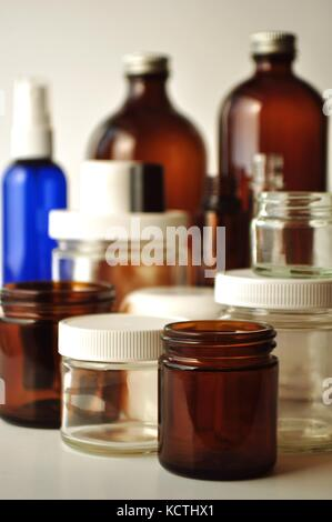 Clear and brown laboratory glass jars and bottles. Containers for essential oils, cosmetics, medication, oils, liquids, - Stock Photo