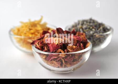 Dried petals of medicinal plants and herbs for cosmetic, nutritional and medical purposes. Close-up in glass jars - Stock Photo