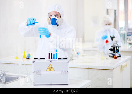 Male researcher wearing hazmat suit adding blue solution to test tube while conducting experiment at modern laboratory - Stock Photo