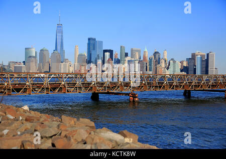 The skyline of Lower Manhattan financial district with foot bridge connect Ellis Island and Liberty State Park over - Stock Photo