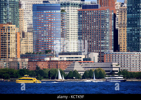 A closed up view of office towers in Lower Manhattan financial district with ferry boats in Hudson River in foreground.New - Stock Photo