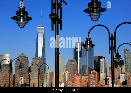 Skyline of Financial District in lower Manhattan with Hudson River and lampposts of old ferry dock of Liberty State - Stock Photo