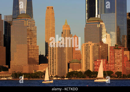 Skyline of Lower Manhattan Financial District with sailboats in Hudson River in foreground under late afternoon sunlight.New York City.USA Stock Photo