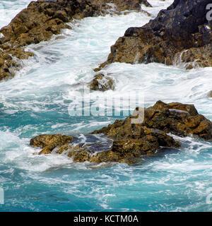 Breaking waves clash against bizarre lava rocks on the coast of Los Hervideros on Lanzarote, Spain. - Stock Photo