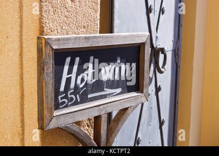 Blackboard sign with chalk letters and arrow  showing direction to the hot wine selling place. - Stock Photo