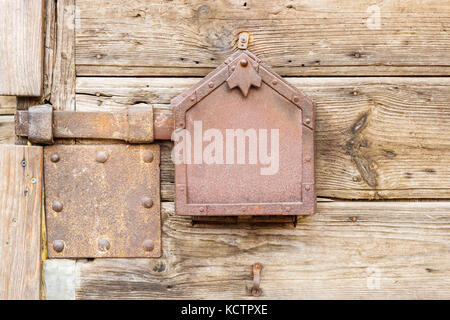 Old wooden doors locked with rusty metal latch - Stock Photo
