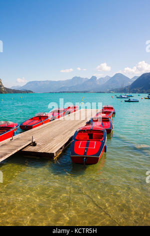 Red boats on transparent water of  alpine lake Wolfgangsee near St.Gilgen, Austria - Stock Photo