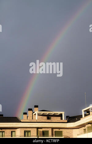 rainbow in a blue sky over the houses of the city after a storm - Stock Photo