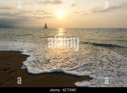 Sunset sailboat is a sailboat sailing along the ocean at sunset with the moon rising in the sky as a wave rolls - Stock Photo