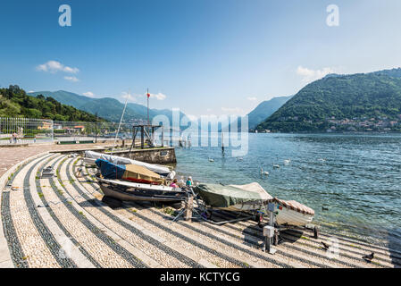 Como, Italy - May 27, 2016: Boats on the shore of Lake Como, city of Como, Italy. Swans on the lake. - Stock Photo