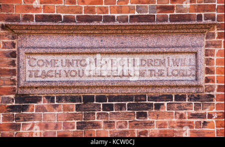 Plaque depicting 'Come unto me ye children, I will teach you the fear of the Lord' on a wall beside Kennaway House,(once - Stock Photo